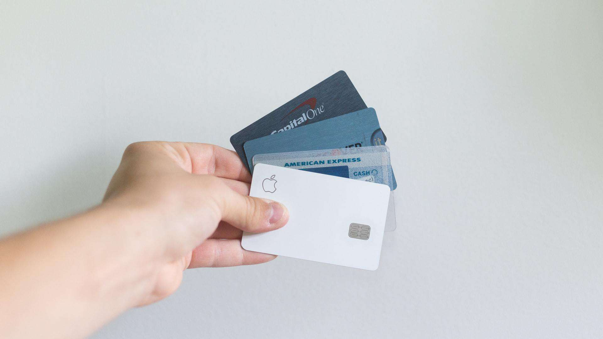 Person holding 4 credit cards